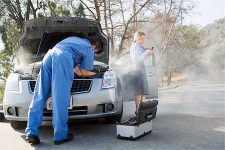 stalled car - Businesswoman using cell phone while mechanic looks at car engine Stock Photo - Premium Royalty-Free, Code: 635-02799968