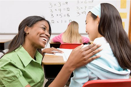 Teacher helping girl with school work Stock Photo - Premium Royalty-Free, Code: 635-02800724