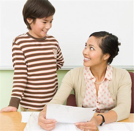 Boy and teacher at teacher's desk Stock Photo - Premium Royalty-Free, Code: 635-02800768