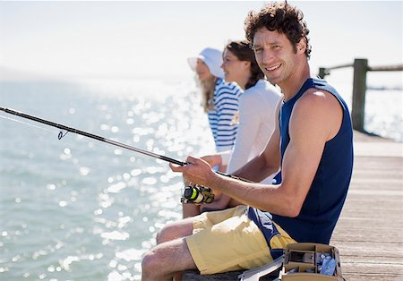 Friends fishing off pier at ocean Stock Photo - Premium Royalty-Free, Code: 635-02942502