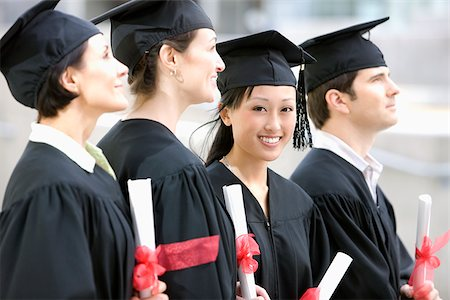 Graduates in caps and gowns holding diplomas Stock Photo - Premium Royalty-Free, Code: 635-02942997