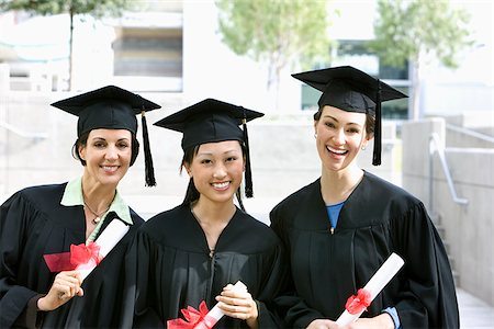 Graduates in caps and gowns holding diplomas Stock Photo - Premium Royalty-Free, Code: 635-02943011