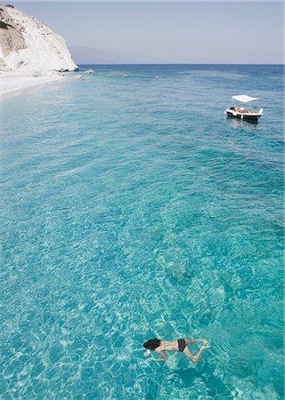 Girl swimming in ocean near beach, Lalaria Beach, Skiathos, Greece Stock Photo - Premium Royalty-Free, Code: 635-02943167