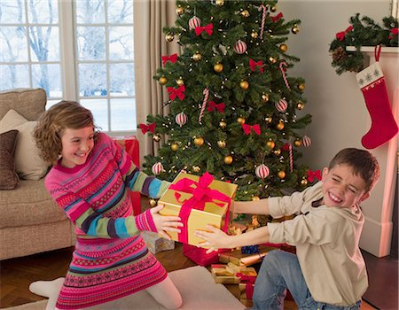 Boy and girl tugging at Christmas gift in living room Stock Photo - Premium Royalty-Free, Code: 635-02990208
