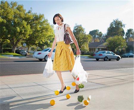 falling - Woman dropping groceries on sidewalk Stock Photo - Premium Royalty-Free, Code: 635-03015340