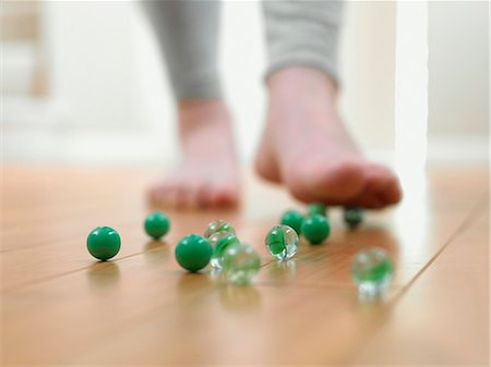 dangerous accident - Child about to slip on marbles on the floor Stock Photo - Premium Royalty-Free, Code: 635-03015384