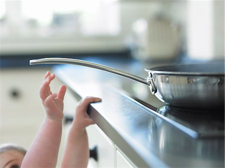 dangerous accident - Baby reaching for hot frying pan on stove Stock Photo - Premium Royalty-Free, Code: 635-03015639