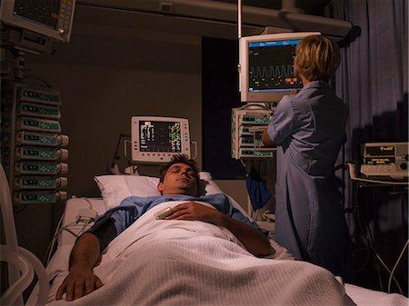 Nurse tending patient in intensive care Stock Photo - Premium Royalty-Free, Code: 635-03161430