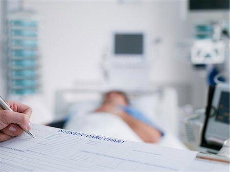 Nurse tending patient in intensive care Stock Photo - Premium Royalty-Free, Code: 635-03161433