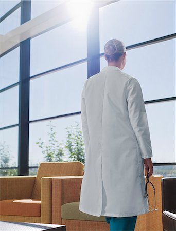 doctor in waiting room - Doctor holding stethoscope in hospital lobby Stock Photo - Premium Royalty-Free, Code: 635-03161518