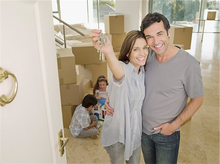 Happy couple holding keys in new house Stock Photo - Premium Royalty-Free, Code: 635-03228824