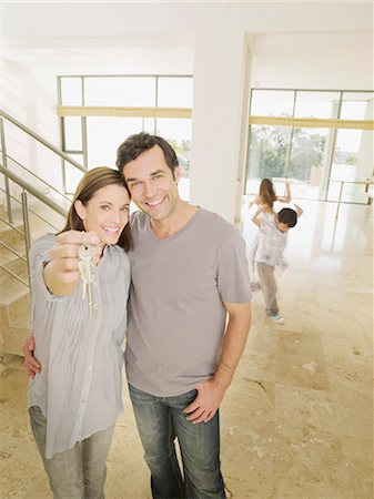 Happy couple holding keys in new house Stock Photo - Premium Royalty-Free, Code: 635-03228820