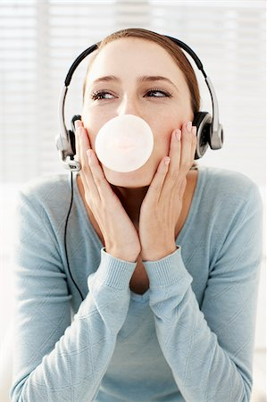 Woman wearing headset and blowing bubble Stock Photo - Premium Royalty-Free, Code: 635-03229155