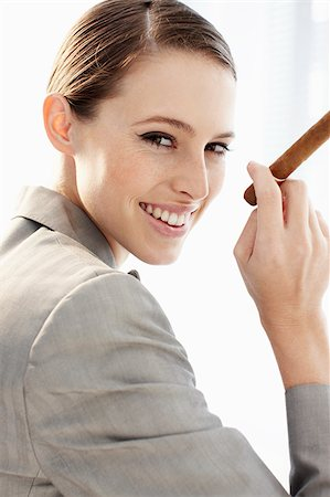 Smiling businesswoman holding cigar Stock Photo - Premium Royalty-Free, Code: 635-03229168