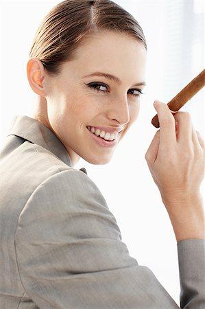 Smiling businesswoman holding cigar Stock Photo - Premium Royalty-Free, Code: 635-03229168