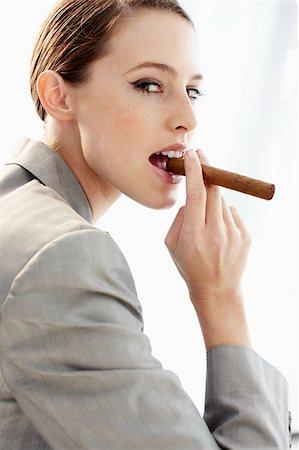 Businesswoman biting cigar Stock Photo - Premium Royalty-Free, Code: 635-03229169