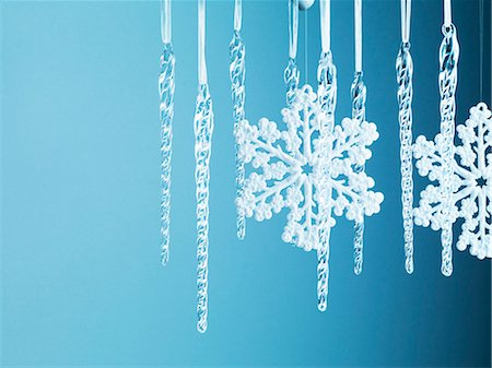snowflakes  holiday - Snowflake and icicle Christmas ornaments hanging from string Stock Photo - Premium Royalty-Free, Code: 635-03372987