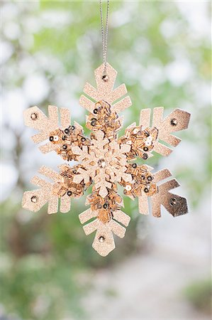 snowflakes  holiday - Close up of snowflake Christmas ornament hanging on string Stock Photo - Premium Royalty-Free, Code: 635-03373025
