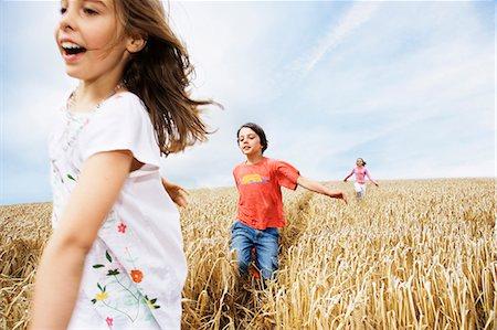 Children running in wheat field Stock Photo - Premium Royalty-Free, Code: 635-03373074