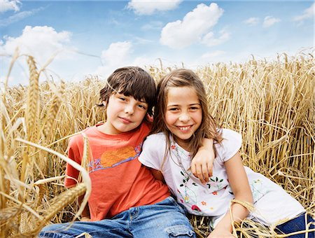 Boy and girl sitting in wheat field Stock Photo - Premium Royalty-Free, Code: 635-03373075