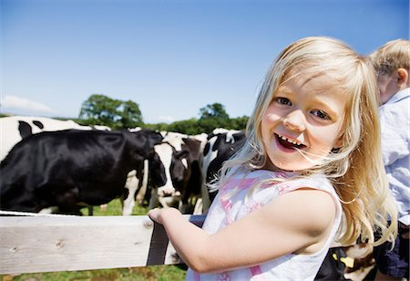 Girl at fence near cows Stock Photo - Premium Royalty-Free, Code: 635-03373092