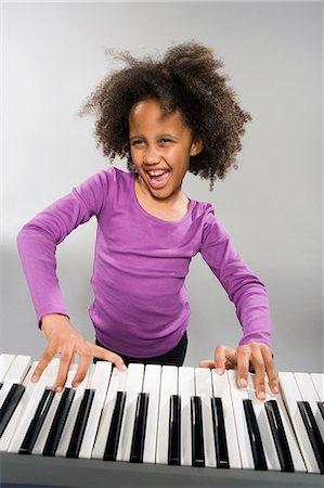 Girl playing piano Stock Photo - Premium Royalty-Free, Code: 635-03373285