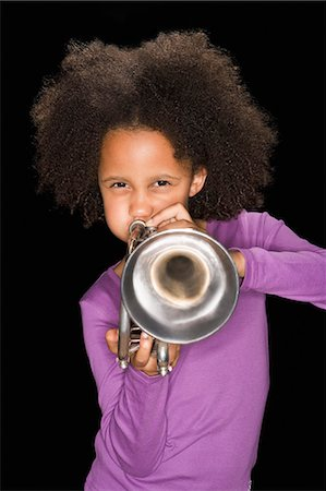 Girl playing trumpet Stock Photo - Premium Royalty-Free, Code: 635-03373286