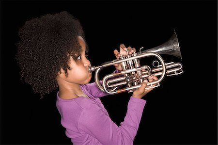 Girl playing trumpet Stock Photo - Premium Royalty-Free, Code: 635-03373287
