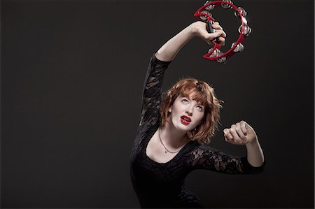 Woman playing tambourine Stock Photo - Premium Royalty-Free, Code: 635-03373290