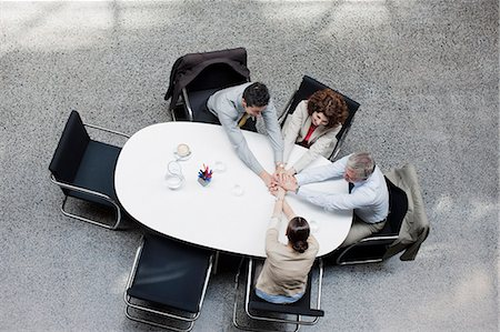 Directly above business people stacking hands at conference table Stock Photo - Premium Royalty-Free, Code: 635-03441193