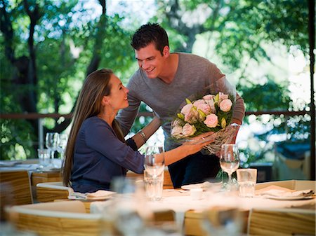 Man giving flowers to woman at restaurant table Stock Photo - Premium Royalty-Free, Code: 635-03441300
