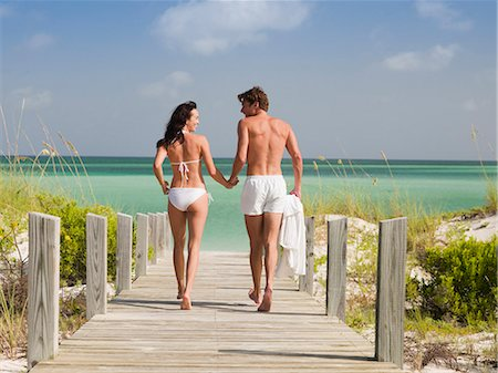 Couple in bathing suits holding hands and walking toward ocean Stock Photo - Premium Royalty-Free, Code: 635-03441310
