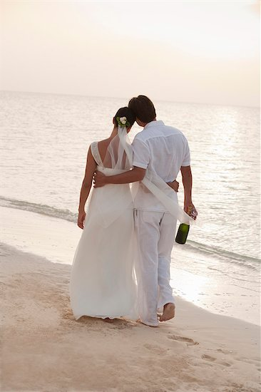 Bride and groom walking on beach with champagne bottle Stock Photo - Premium Royalty-Free, Image code: 635-03441342