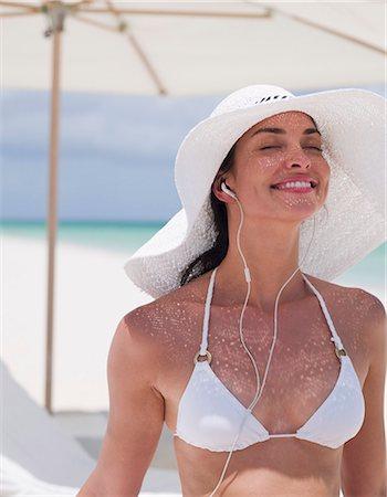 Woman in bikini wearing sun hat and listening to headphones on beach Stock Photo - Premium Royalty-Free, Code: 635-03441350