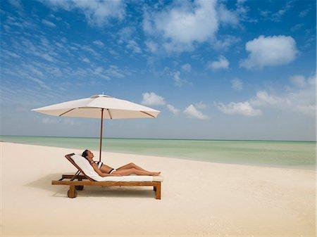 Woman laying on lounge chair under beach umbrella Stock Photo - Premium Royalty-Free, Code: 635-03441376