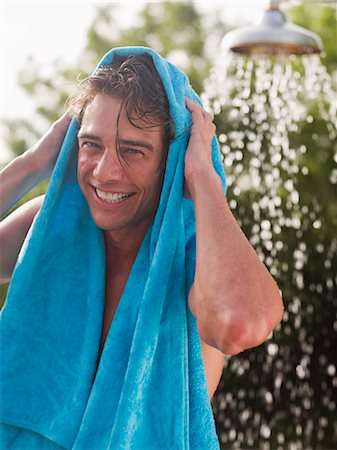 Man drying hair with towel near outdoor shower Stock Photo - Premium Royalty-Free, Code: 635-03441377