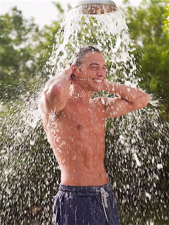 Man standing under outdoor shower Stock Photo - Premium Royalty-Free, Code: 635-03441378