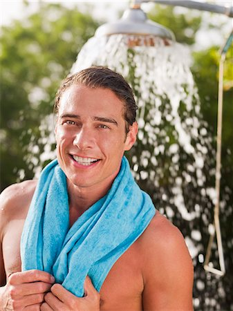 Man with towel around neck near outdoor shower head Stock Photo - Premium Royalty-Free, Code: 635-03441379