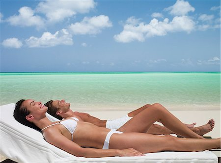 Couple sunbathing on lounge chairs on beach Stock Photo - Premium Royalty-Free, Code: 635-03441373