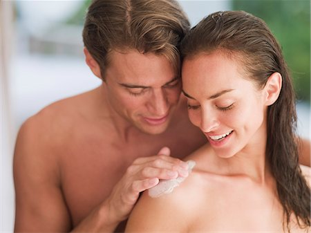 Man applying lotion to woman's shoulder Stock Photo - Premium Royalty-Free, Code: 635-03441418