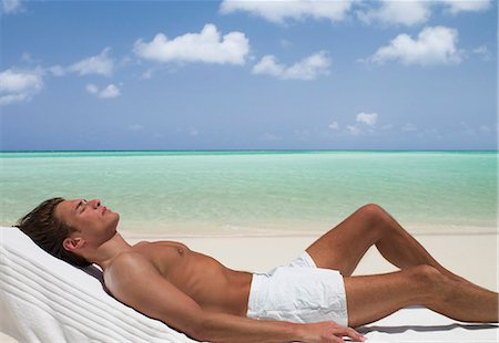 Man on beach sunbathing on lounge chair with eyes closed Stock Photo - Premium Royalty-Free, Code: 635-03441410