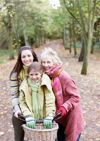 Grandmother, mother and daughter riding bicycles in park Stock Photo - Premium Royalty-Free, Code: 635-03457389