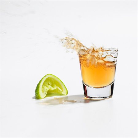 Close up of tequila splashing out of glass Stock Photo - Premium Royalty-Free, Code: 635-03457750