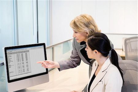 supervising - Businesswoman reviewing co-worker's work on monitor Stock Photo - Premium Royalty-Free, Code: 635-03457837