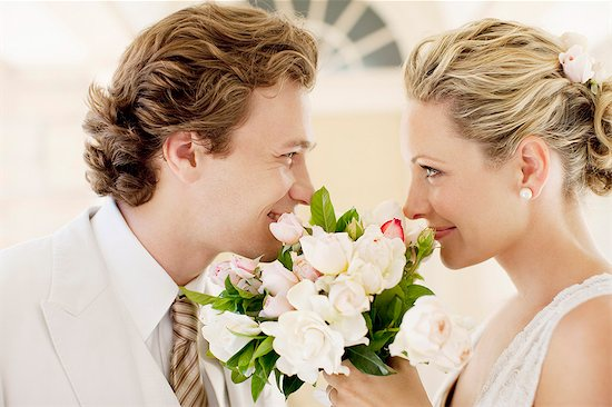 Bride and groom smelling bouquet Stock Photo - Premium Royalty-Free, Image code: 635-03515473