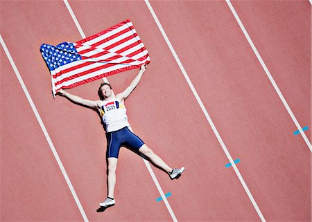 Runner laying on track with American flag Stock Photo - Premium Royalty-Free, Code: 635-03515634