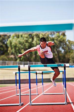 Runner jumping hurdles on track Stock Photo - Premium Royalty-Free, Code: 635-03515689