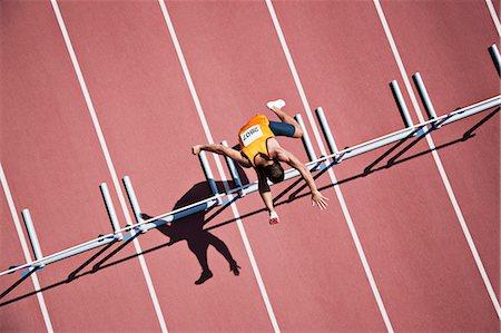 Runner jumping hurdles on track Stock Photo - Premium Royalty-Free, Code: 635-03515699