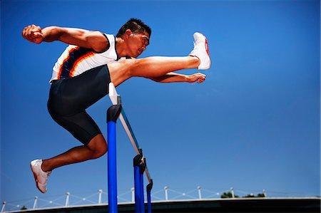 Runner jumping hurdles on track Stock Photo - Premium Royalty-Free, Code: 635-03515690