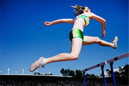 Runner jumping hurdles on track Stock Photo - Premium Royalty-Free, Code: 635-03515691